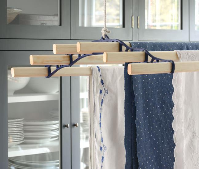 Our six wooden lath Pulley Maid laundry drying rack suspended from the ceiling in a traditional utility room setting. The rack end is cast in blue.